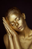 Portrait unearthly Golden girls, hands near the face. Very delicate and feminine. The eyes are closed. Stock Photo