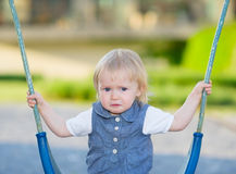 Portrait of unhappy baby sitting on swing Royalty Free Stock Images