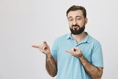 Portrait of unhappy bearded guy with gloomy smile, pointing left with index fingers, over gray background. I am not Stock Photo