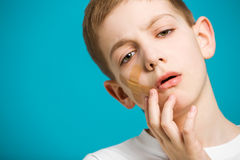 Portrait of unhappy boy with adhesive plaster on his ch Royalty Free Stock Photography
