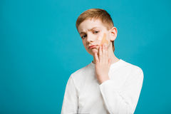 Portrait of unhappy boy with adhesive plaster on his cheek Royalty Free Stock Photo