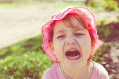 Portrait of an unhappy child. Baby screams. The child is angry stock photos