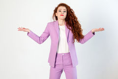 Portrait of  unhappy confused business woman with red - brown hair and makeup in pink suit. looking at camera Stock Photo