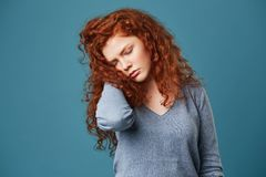 Portrait of unhappy frustrated girl with red wavy hair and freckles holding hand in hair with closed eyes having Stock Images
