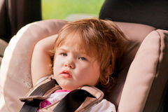 Portrait of unhappy litle kid in safety seat Royalty Free Stock Images