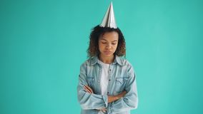 Portrait of unhappy mixed race girl in party hat standing with arms crossed stock video footage