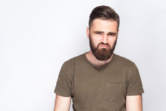 Portrait of unhappy sad bearded man with dark green t shirt against light gray background. Stock Photos
