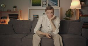 Portrait of unhappy student clicking remote control watching tv in dark room stock video
