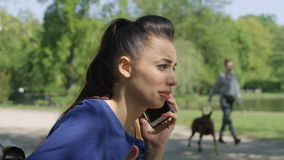 Portrait of unhappy upset young woman talking on mobile phone in sunny park. stock video