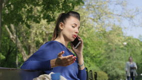 Portrait of unhappy upset young woman talking on mobile phone in sunny park. stock footage