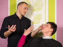 Portrait of unhappy young male at the hairdressing salon royalty free stock photography