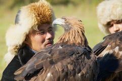 Portrait of unidentified Kazakh hunters holding golden eagles Aquila chrysaetos, circa Almaty, Kazakhstan. Stock Photos