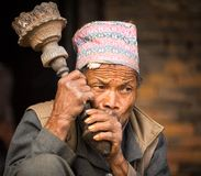 Portrait of unidentified Nepalese man smokes on the street, in Bhaktapur, Nepal. BHAKTAPUR, NEPAL - DEC 7:  Portrait of unidentified Nepalese man smokes on the Royalty Free Stock Photography