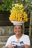 Portrait of unidentified woman together with bananas on her head on the market Royalty Free Stock Images