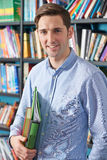 Portrait Of University Student In Library. University Student Reads Textbook In Library Stock Photo
