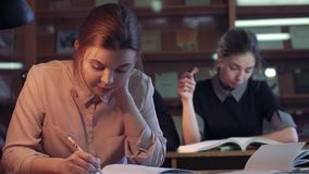 Portrait of university students studying in library. Portrait of university students studying in quite library stock footage