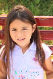 Portrait of unlucky girl. Face of an unhappy little girl with long hair in lila t-shirt Royalty Free Stock Photo