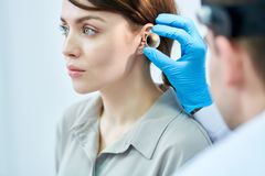 Audiologist Examining Ears. Portrait of unrecognizable doctor examining ears and hearing of beautiful young woman royalty free stock photo