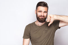 Portrait of unsatisfied bearded man with thumbs down and dark green t shirt against light gray background. Royalty Free Stock Photography