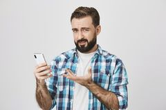 Portrait of unsatisfied man holding smartphone and gesturing with another hand, expressing dislike and disappointment. While looking at camera, standing over Royalty Free Stock Images