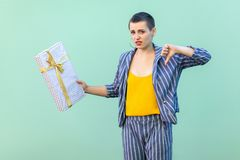 Portrait of unsatisfied with short hair young woman in striped suit standing, showing dislike gesture to her present box, looking. At camera. Indoor, isolated royalty free stock photo