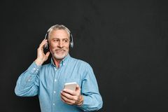 Portrait of unshaved male pensioner 60s with gray hair holding c. Ellphone and listening to music via wireless headphones isolated over black background Stock Photos