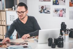 Cheerful bearded man looking at photos. Portrait of unshaven happy designer choosing images while working at desk in office. Occupation concept Royalty Free Stock Image