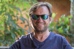 Portrait of an unshaven middle-aged man in sunglasses relaxing on the nature in summer day royalty free stock photo