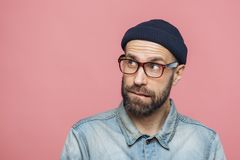 Portrait of unshaven thoughtful middle aged male with pensive expression looks upwards, wears stylish hat, eyewear and denim jacke royalty free stock image