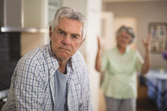 Portrait of unsmiling senior man with angry woman in background. Portrait of unsmiling senior men with angry women in background at home Stock Image