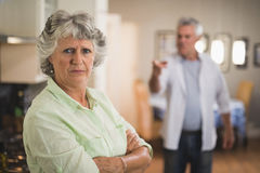 Portrait of unsmiling senior woman with angry man in background. Portrait of unsmiling senior women with angry men in background at home Royalty Free Stock Photos