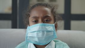 Ill girl wearing mask to prevent spread of germs