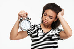 Portrait of an upset african girl looking at alarm clock. Portrait of an upset frustrated african girl looking at alarm clock isolated over white background Stock Photography