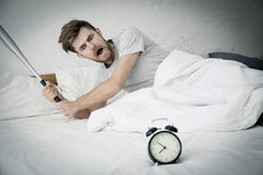 Portrait upset angry with baseball hit young man screaming at alarm clock. On bedroom. Employee running late. Time management with business concept Stock Images