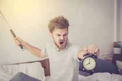 Portrait upset angry with baseball hit young man screaming at alarm clock on bedroom. Employee running late. Time management with business concept Stock Images