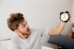 Portrait upset angry young man screaming at alarm clock. On bedroom. Employee running late -  Time management with business concept Royalty Free Stock Photo