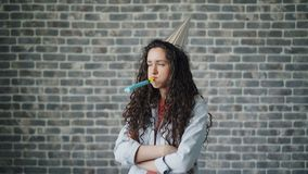 Portrait of upset birthday girl in party hat blowing whistle standing alone stock video
