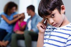Portrait of upset boy. Close-up of upset boy, family in background Stock Photo