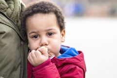 Portrait of an upset boy in his mother`s arms with tears in his eyes. Eating apple for comfort royalty free stock image