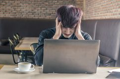 Portrait of an upset businessman at desk in cafe. Businessman being depressed by working in cafe. Royalty Free Stock Photo