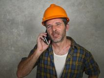 Portrait of upset construction worker or stressed contractor man in builder hat talking on mobile phone unhappy in stress messing stock photos