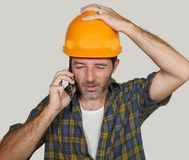 Portrait of upset construction worker or stressed contractor man in builder hat talking on mobile phone unhappy in stress messing royalty free stock photos