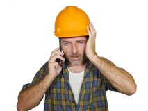 Portrait of upset construction worker or stressed contractor man in builder hat talking on mobile phone unhappy in stress messing stock photo