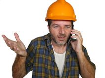 Portrait of upset construction worker or stressed contractor man in builder hat talking on mobile phone unhappy in stress messing royalty free stock image