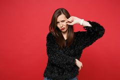 Portrait of upset crying young woman in black fur sweater standing and wiping tears isolated on bright red wall royalty free stock image
