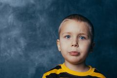 Portrait of an upset cute little child looking at camera against concrete wall background royalty free stock image