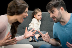 Portrait of upset daughter and arguing parents on black. Family problems concept Royalty Free Stock Image