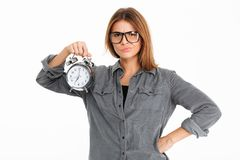 Portrait of an upset disappointed girl in eyewear. Holding alarm clock isolated over white background Stock Photography