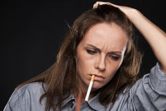 Portrait of upset female holding cigarette. Royalty Free Stock Image