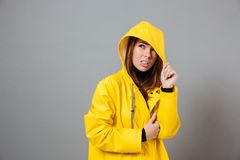 Portrait of an upset girl dressed in raincoat posing. With hood on her head  over gray background Royalty Free Stock Photo